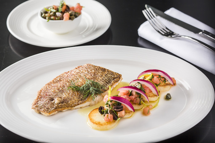 Baked red snapper fillet cooked in Mediterranean sauce