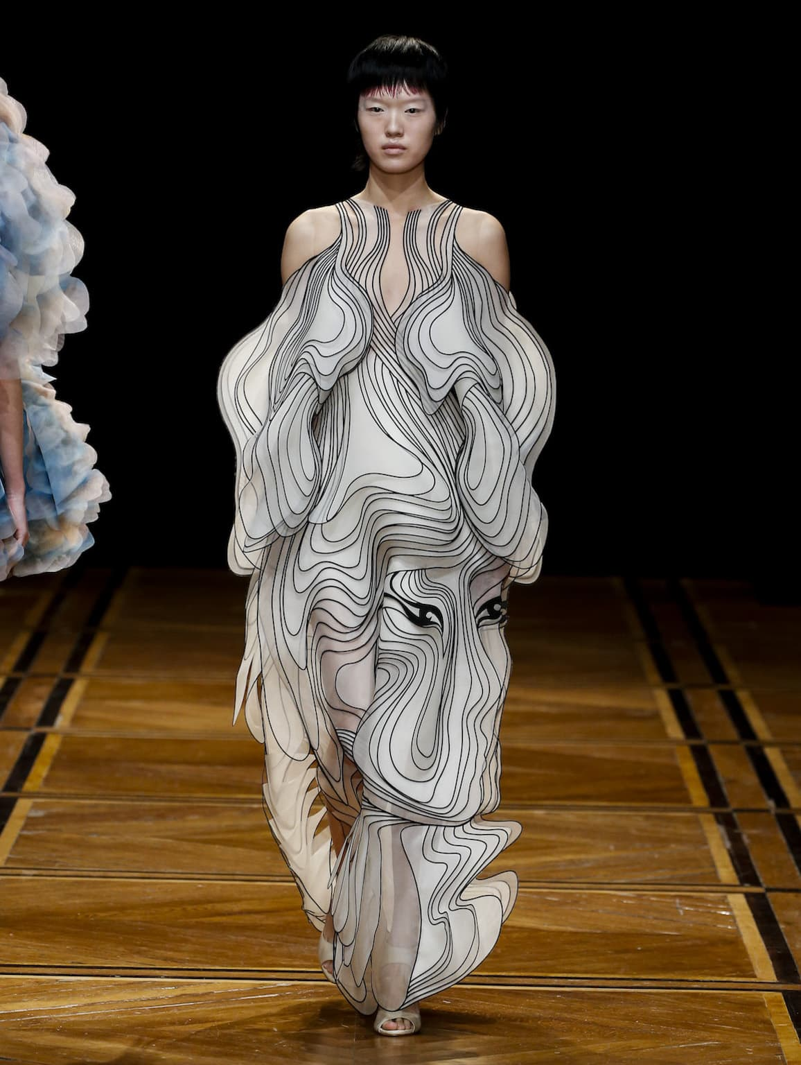 To achieve the affect of a moving 3D wave drawing, van Herpen incorporated  organzas of various length and volume throughout the collection. db9b257728