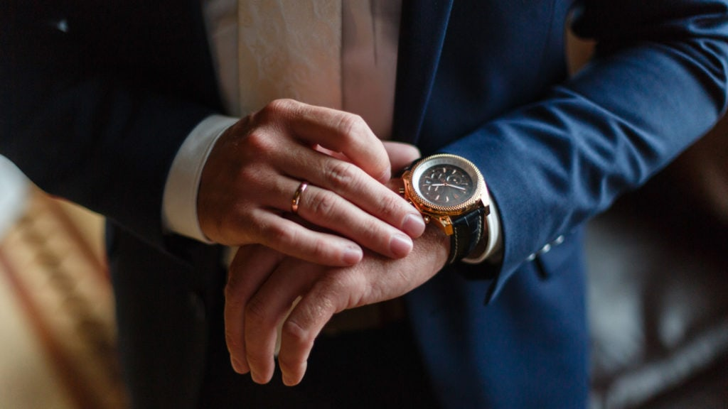 Navy suit against a Yellow Gold cased watch